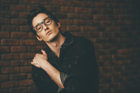 Male beauty, fashion. Handsome young man posing in spectacles and black denim jacket by the brick wall. Hair styling.
