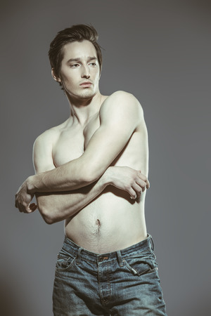 Portrait of a sexy young man with slender body posing at studio in jeans. Gray background. Mens health. Stock Photo