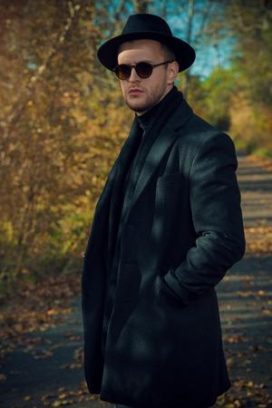 Modern handsome man in the autumn park. Seasonal fashion.