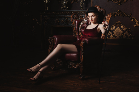 Gorgeous young woman in velvet red dress is sitting in the armchair in a luxury apartment. Classic vintage interior. Beauty, fashion. Фото со стока