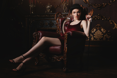 Gorgeous young woman in velvet red dress is sitting in the armchair in a luxury apartment. Classic vintage interior. Beauty, fashion. Stock Photo