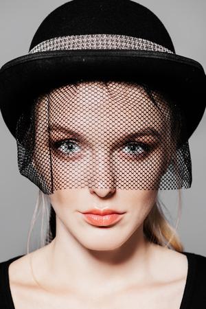 Adatti il colpo di una giovane donna sbalorditiva in cappello con un velo. Stile copricapo.