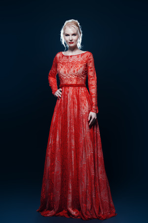Portrait of a beautiful sexy girl in red long dress over black background. Full length portrait. Beauty, fashion. Studio shot.
