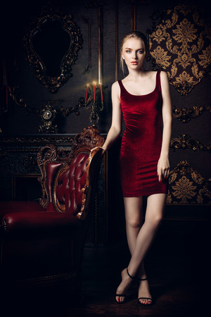 Gorgeous young woman in velvet red dress posing in a luxury apartment. Classic vintage interior. Beauty, fashion.