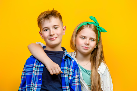 Portrait of two emotional children on a bright yellow background. Kid's fashion. Фото со стока
