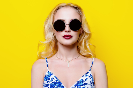 Attractive young woman wearing bright clothes and sunglasses over yellow background.
