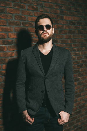 Fashion shot of a stylish brutal bearded man posing in jacket and sunglasses. Studio shot over brick wall.