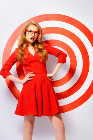 Gorgeous fashion model in red dress and elegant red glasses posing over red circles of the target.