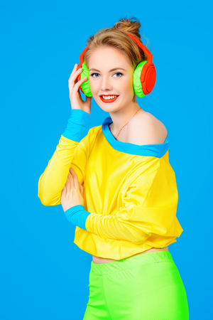 Trendy girl in bright colorful clothes listening to music in headphones.