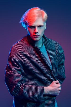 Portrait of a handsome young man with blond hair wearing in a plaid coat, posing at studio over gray background. Mens beauty and health.