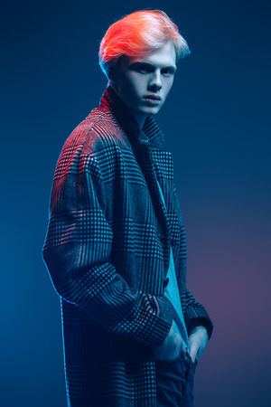 Portrait of a handsome young man with blond hair wearing in a plaid coat, posing at studio over gray background. Men's beauty and health.