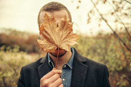 Seasonal autumn fashion. Portrait of a man covering his face with an autumn leaf. Autumn nature.