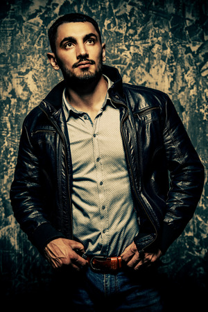 Portrait of a handsome man in a leather jacket on a grunge background. Studio shot. Mens beauty, fashion. Mens barbershop.