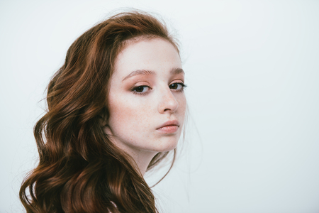 Close-up portrait of a  fifteen-year-old girl with long curly red hair over white background. Beauty, fashion.