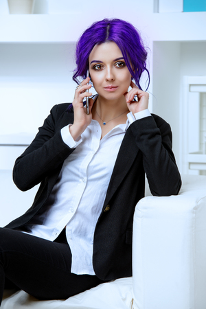 Elegant businesswoman with purple hair talking on her cell phone at the office. Contemporary business.