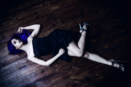 Attractive young woman in black dress with purple hair lying on a wooden floor. Beauty, youth fashion. Hair coloring. Cosmetics, make-up.