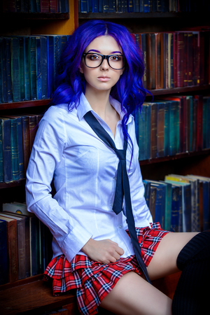 Pretty student girl with long purple hair posing in school clothes by the bookshelves.
