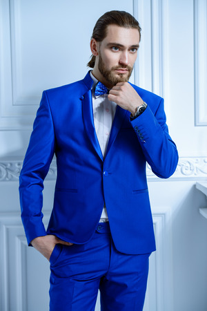 Fashion shot. Handsome young man posing in elegant blue suit in luxurious apartments. Hair styling, barbershop. Mens beauty, fashion.