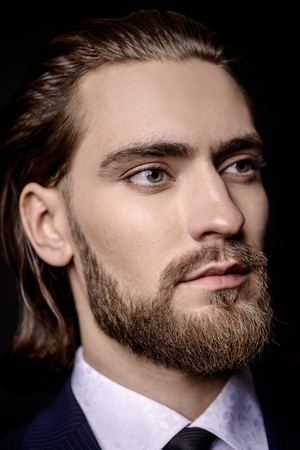 Close-up portrait of a bearded handsome young man in elegant clothes. Male beauty, fashion. Hair styling, barbershop.