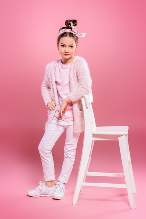 Children's fashion. Cheerful seven year old girl wearing pink cardigan posing over pink background. Studio shot. Фото со стока