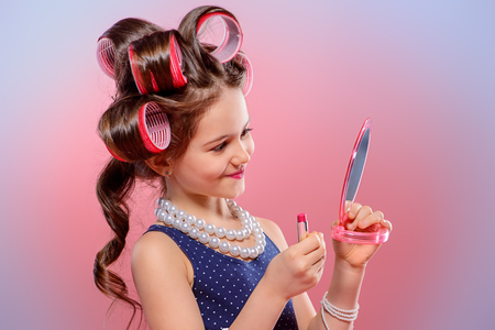 Portrait of a pretty little girl with curlers in her hair holding lipstick and mirror. Studio shot over pink background. Kids fashion.