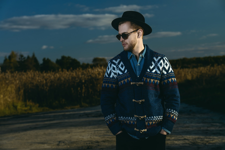 Autumn fashion. Portrait of a handsome man wearing cardigan and hat standing outdoor over autumn nature background.