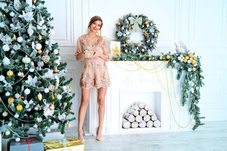 Navidad, concepto de vacaciones de invierno. Hermosa mujer encantadora en traje de noche posando en lujosos apartamentos decorados para Navidad. Belleza, moda.