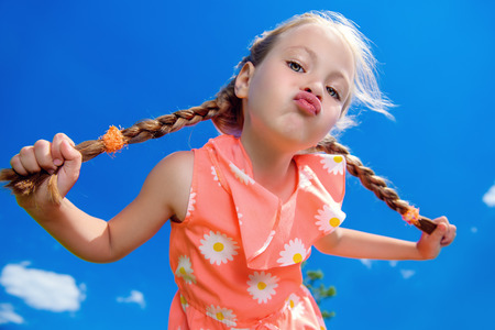 Happy little girl in beautiful dress over blue sky. Children's fashion. Happy summer holidays. 版權商用圖片