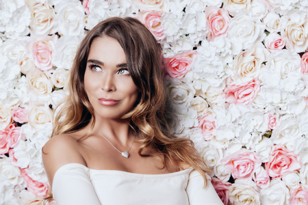 Portrait of a beautiful young woman over floral background. Spring mood. Summer fashion. Natural cosmetics, make-up, skincare.