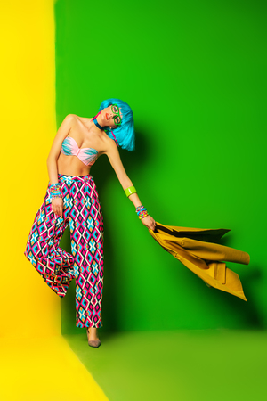 Full length portrait of a fashion girl with blue hair wearing bright summer clothes over yellow and green background. Beauty, fashion concept.  Pin-up style. Reklamní fotografie