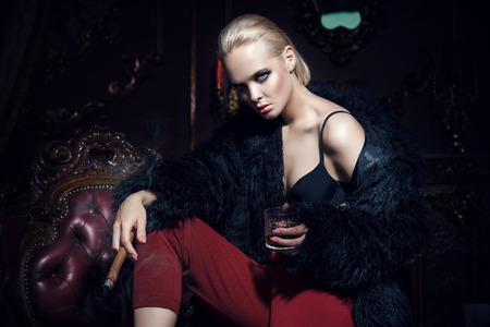 Seductive girl sitting on a leather armchair, drinks whiskey and smokes a cigar in a luxurious vintage interior. Fashion shot. Stock Photo