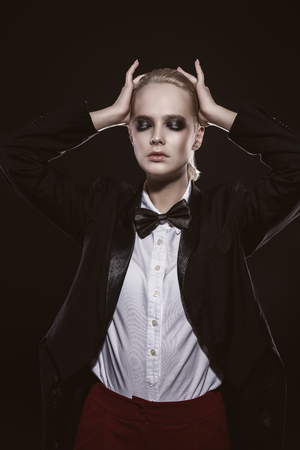 Fashion shot. Attractive young model posing in a mans jacket and shirt with bow-tie. Mans style clothing. Black background.