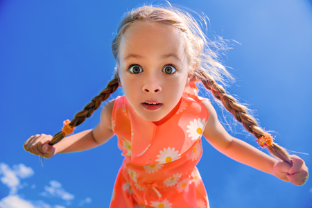 Happy little girl with pigtails in beautiful dress over blue sky. Children's fashion. Happy summer holidays. Foto de archivo