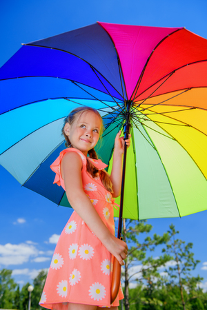 Portrait of a cheerful little girl in beautiful dress with colorful umbrella over blue sky on a sunny summer day. Happy childhood.