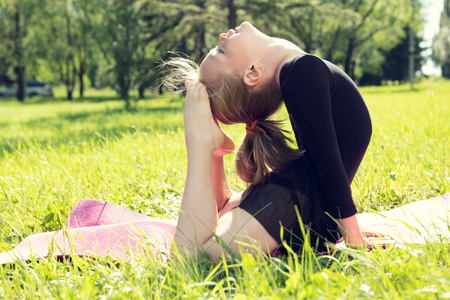 Beautiful little girl doing yoga in the summer park. Healthy lifestyle. Various yoga postures. Imagens