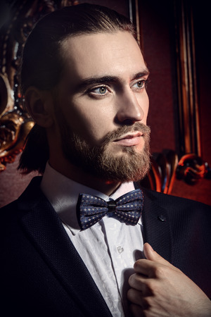 Portrait of a well-dressed imposing man in elegant suit posing in apartments with luxurious classic interior. Mens beauty, fashion. Hair styling, barbershop.