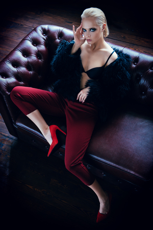 Seductive girl in the black bra, red pants and  fur jacket sitting on a leather sofa. Luxurious lifestyle. Fashion, beauty. Studio shot.