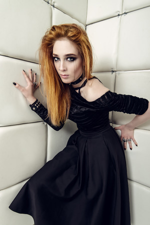 Portrait of a beautiful crazy girl dressed in black gothic dress in an isolated room in a madhouse.