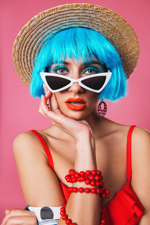 Close-up portrait of a funny girl with bright blue hair wearing pin-up sunglasses over pink background.  Beauty, fashion concept.  Pin-up style. Stock Photo