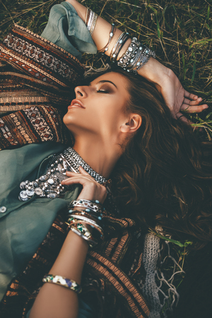 Beautiful hippie girl lying in a grass. Modern boho style. Beauty, fashion, Zdjęcie Seryjne - 106997223