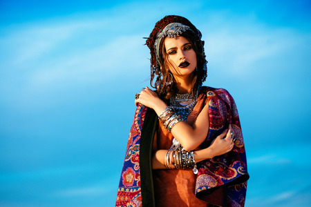 Magnificent fashion woman posing in boho style clothes in the rays of the sunset. Outdoor fashion. Gypsy style. Banque d'images