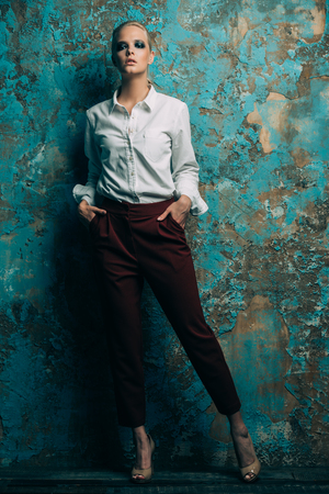 Fashion shot. Attractive young model posing in a white shirt and red trousers. Man's style clothing. White background. Archivio Fotografico - 106457841