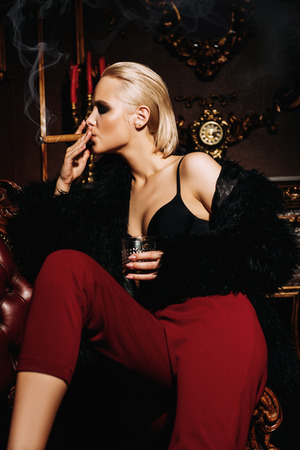 Seductive girl sitting on a leather armchair, drinks whiskey and smokes a cigar in a luxurious vintage interior. Fashion shot. Stok Fotoğraf