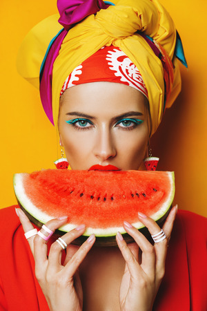 Fashionable woman with bright make-up eating watermelon. Yellow background. Beauty, fashion, make-up concept. Stok Fotoğraf - 106457913