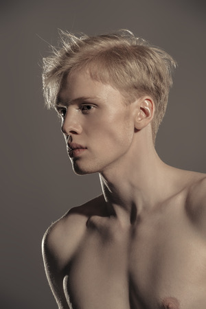 Portrait of a shirtless young man with blond hair posing at studio over grunge background. Men's beauty and health.