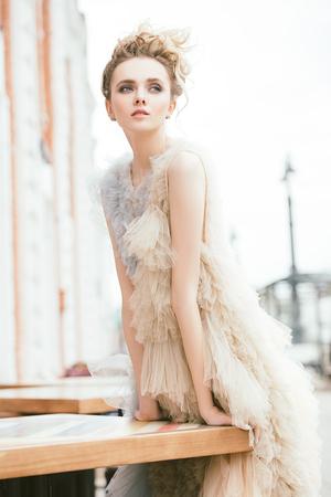 Beautiful young woman in an elegant fluffy dress posing on street. Beauty, street fashion. Stock Photo
