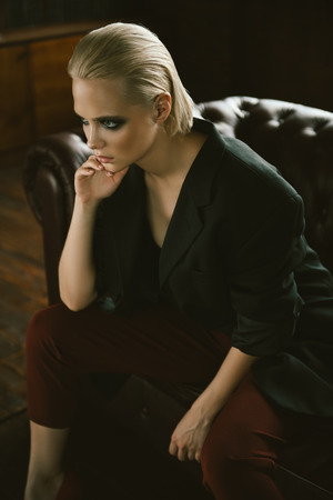 Seductive girl in the black jacket, red pants sitting on a leather sofa. Luxurious lifestyle. Fashion, beauty. Studio shot.