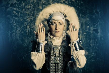 Mature woman in ethnic costume posing in studio.