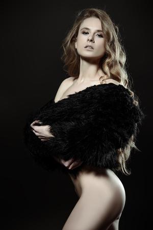 Ragazza nuda in una pelliccia nera in posa su uno sfondo nero. Silhouette femminile. Giovane donna con lunghi capelli ricci.