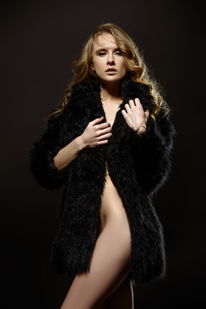 Nude girl in a black fur coat posing on a black background. Female nude silhouette. Young sexy woman with long curly hair.